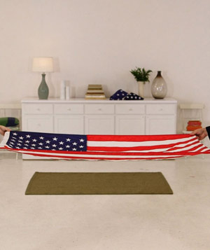 Woman and man starting to fold the American flag