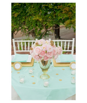 Pink floral wedding centerpiece with mint green linens and gold accents