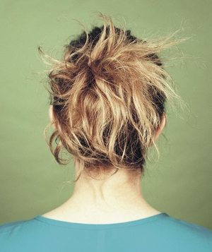 Woman's hair in messy knot hairstyle, back view