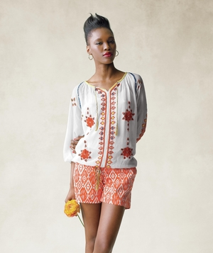 Model wearing peasant blouse and patterned shorts