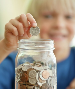 Little boy saving coins in jar