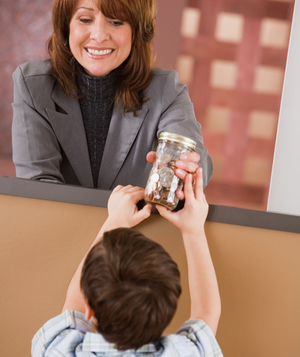 Little boy handing jar of coins to bank teller