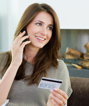 Woman shopping over the phone and holding credit card