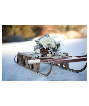 Wintry wedding bouquet sitting on small sleigh in snow