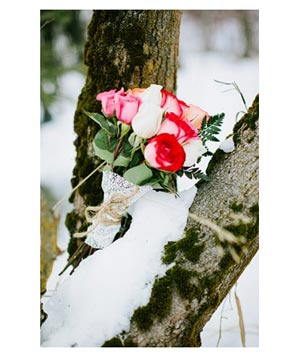 Wedding bouquet of roses sitting in a tree with snow