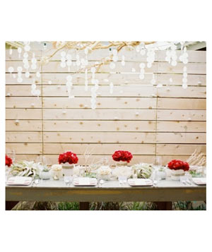Outdoor table with red accents and branches hung with lights