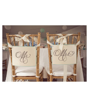 Gold chairs at wedding table with Mr. and Mrs. signs