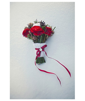 Wedding bouquet with red roses, pinecones, and a hand-knit band with a ribbon