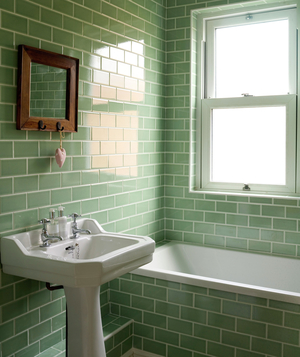 Bathroom with green tiles and pedestal sink