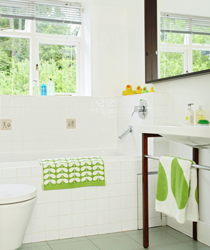 White Bathroom With Green Accents And Oversized Wood Framed Mirror
