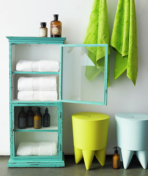 Bathroom with bright turquoise storage cabinet and other bright accessories