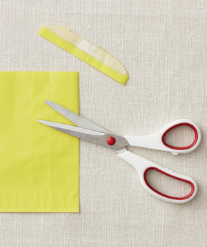Scissors cutting yellow envelope bag