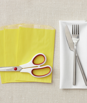 Yellow envelope bags, scissors, and a fork and knife on a white napkin