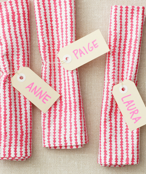 Patterned cloth napkins with names on office supply tags