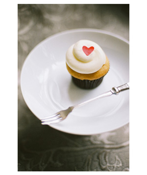 Cupcake with white frosting and simple red heart