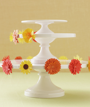 White cake stand halfway decorated by orange and yellow floral stickers