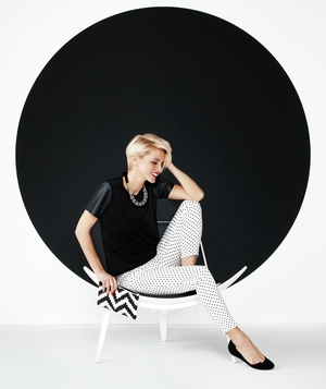 Model wearing black top and white pants with black dots