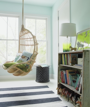Pale blue bedroom with wicker swing, striped rug