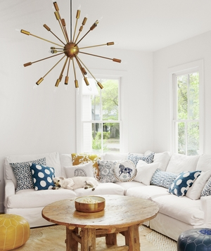 Family room with white sectional, blue and white throw pillows, cowhide rug, bold light fixture