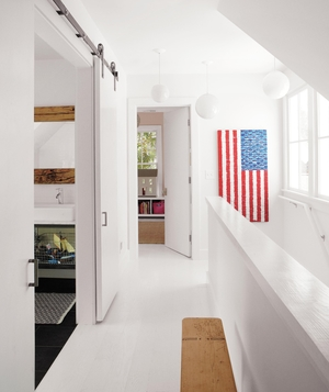 White hallway with sliding barn doors, flag