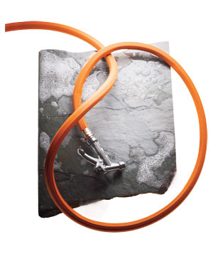 Orange hose with suds on piece of slate