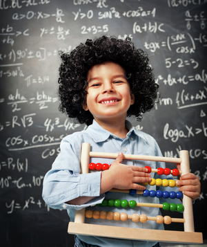 Little boy in front of chalkboard holding abacus and smiling