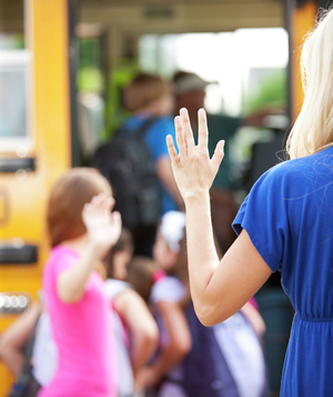 Mother waving goodbye to daughter getting on school bus