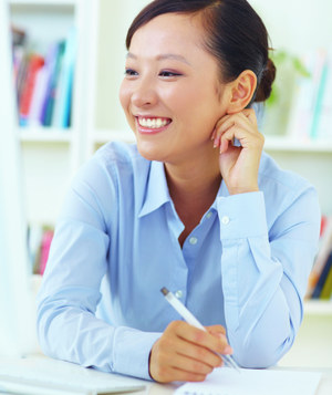 Woman in blue shirt smiling and taking notes