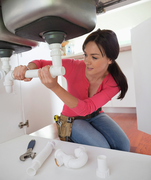 Woman fixing pipes under kitchen sink