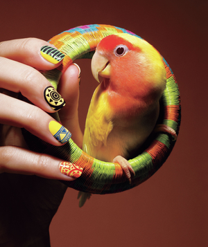 Hand with nail art holding woven bracelet with lovebird