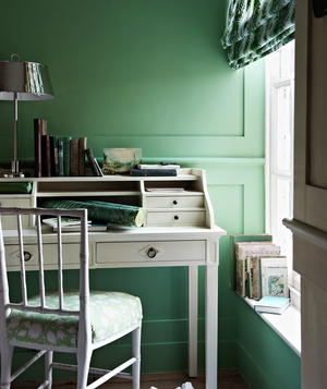 Room with green walls and white desk