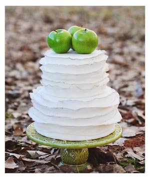White wedding cake with green apples on top