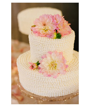 Wedding cake covered in frosting pearls and topped with pink flowers