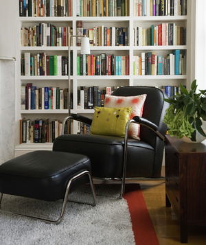 Room with built-in white bookshelf and black leather armchair