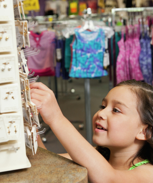 Little girl looking at earrings in store