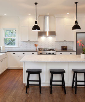 White kitchen with black fixtures, stools
