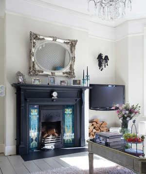 Room with ornate mirror over fireplace and chandelier