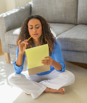 Woman on floor cross-legged with pencil and legal pad, working at home