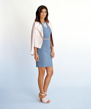 Model wearing slate blue dress and light pink jacket