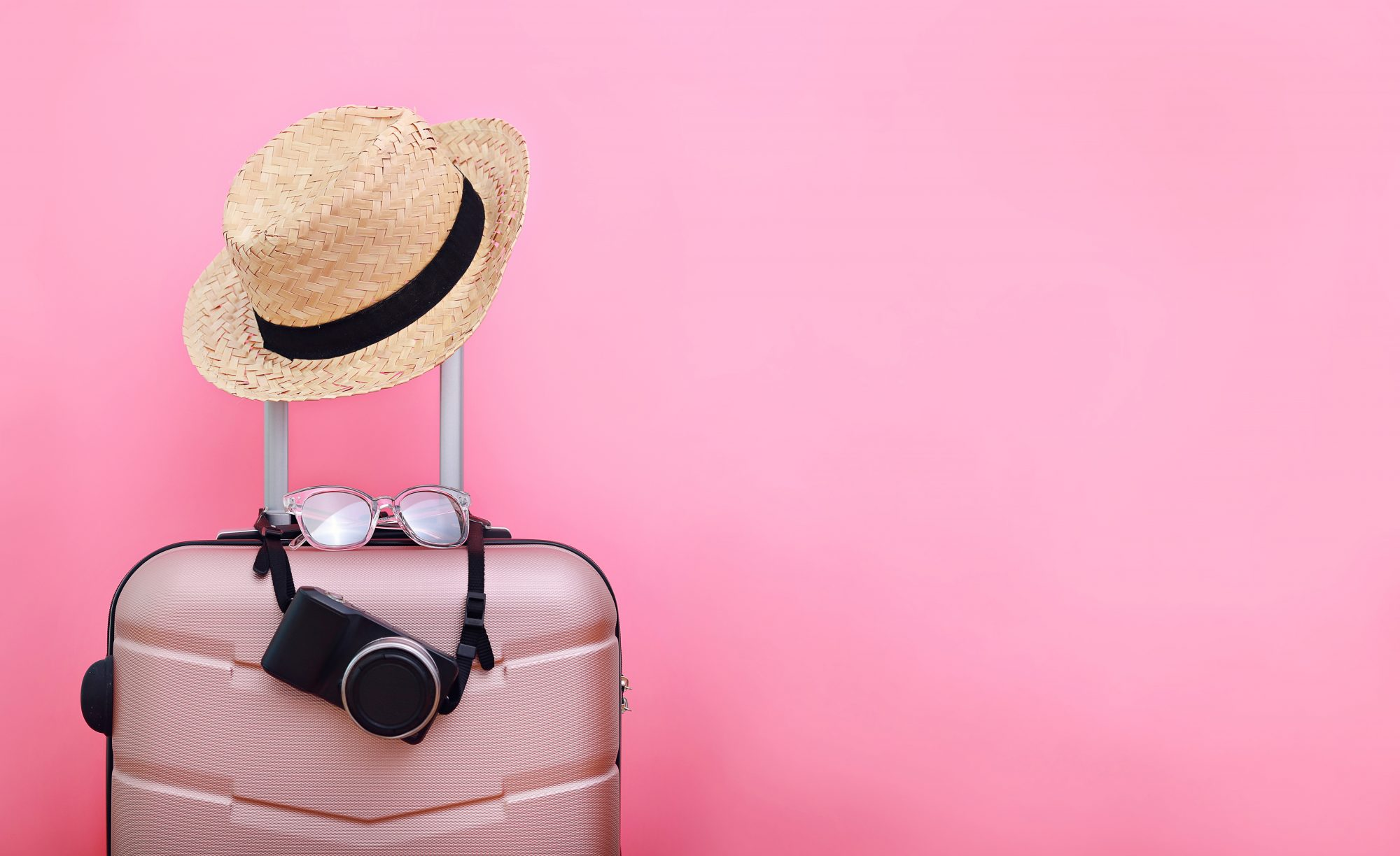pink suitcase, hat, sunglasses, and camera on a pink background