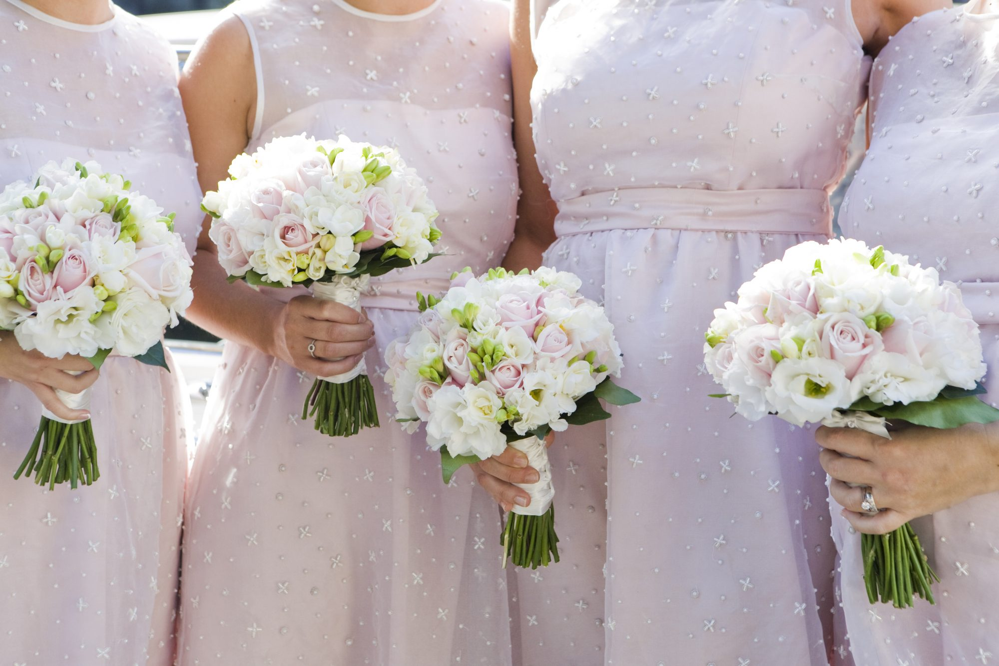 Bridesmaids in pink dresses holding bouquets