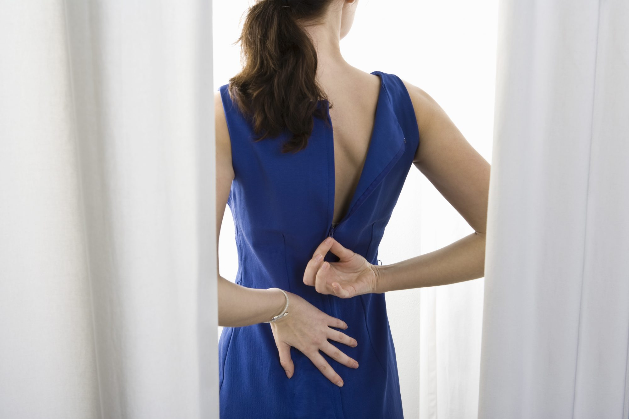 Woman zipping up a blue dress in dressing room