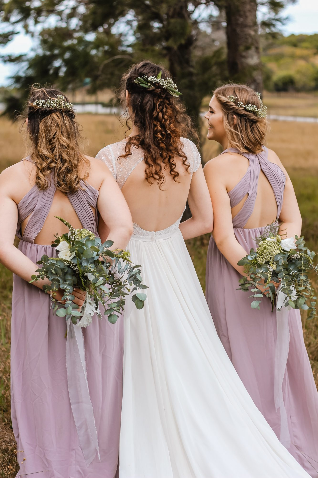 Bride and bridesmaids walking away holding bouquets