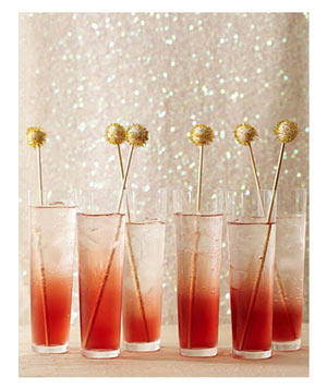 Red cocktails with gold swizzle sticks