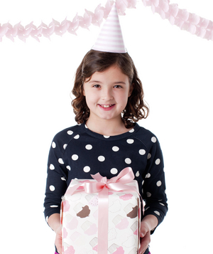 Girl holding present wearing birthday hat