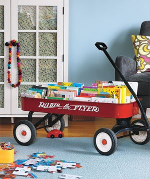 Little red wagon filled with books in living room with jumbo puzzle pieces on floor