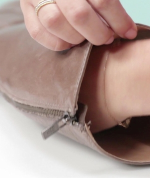 Hands stuff newspaper into leather boots