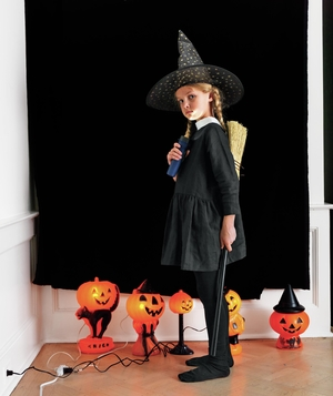 Girl in witch costume with pumpkin lights