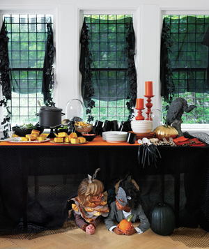 Kids under Halloween party table
