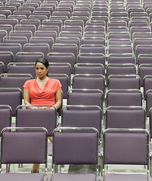 Woman sitting alone in auditorium